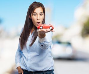 surprised young woman with red car
